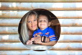 Mother and son peeks through hole at playground Royalty Free Stock Photography