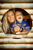Mother and son peeks through hole at playground Stock Photography