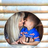 Mother and son peeks through hole at playground Stock Photos