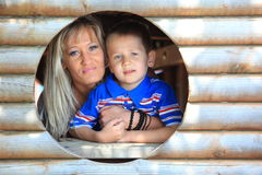 Mother and son peeks through hole at playground Stock Images