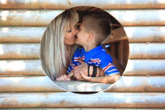 Mother and son peeks through hole at playground Stock Image