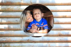 Mother and son peeks through hole at playground Royalty Free Stock Photos