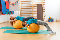 mother and son perform gymnastic exercises Royalty Free Stock Photo