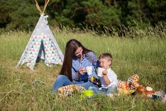 Mother and son at a picnic outdoors eating holiday. Mother and son at a picnic outdoors eating stock image
