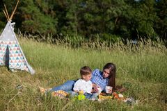 Mother and son at a picnic outdoors eating holiday. Mother and son at a picnic outdoors eating royalty free stock photography