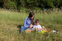 Mother and son at a picnic outdoors eating holiday look. Mother and son at a picnic outdoors eating holiday royalty free stock images