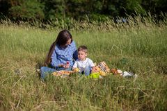Mother and son at a picnic outdoors eating holiday look. Mother and son at a picnic outdoors eating holiday royalty free stock photography