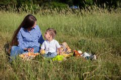 Mother and son at a picnic outdoors eating holiday look. Mother and son at a picnic outdoors eating holiday stock photos