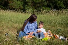 Mother and son at a picnic outdoors eating holiday look. Mother and son at a picnic outdoors eating holiday stock photo