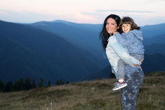 Mother and son piggyback in the mountains Stock Photo