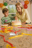 Mother and son (4-6) placing candles on birthday cake at home, smiling (surface level) Stock Photos