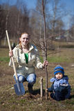 Mother and son  planting  tree. Mother and son with spade outdoors planting  tree Royalty Free Stock Photography