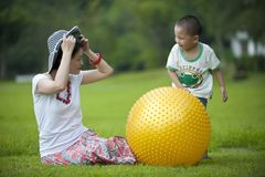 Mother and son play ball in grass Royalty Free Stock Images
