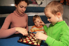 Mother and son play chess. In train`s compartment Stock Photography
