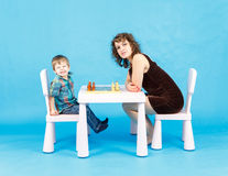 Mother and son play chess. Family and education concept. Mother and son play chess in studio. Family and education concept Stock Image