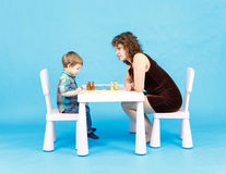 Mother and son play chess. Family and education concept. Mother and son play chess in studio. Family and education concept Stock Photo