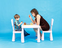 Mother and son play chess. Family and education concept. Mother and son play chess in studio. Family and education concept Royalty Free Stock Images