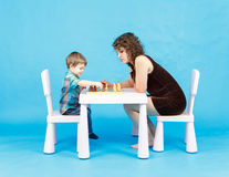 Mother and son play chess. Family and education concept. Mother and son play chess in studio. Family and education concept Stock Photos