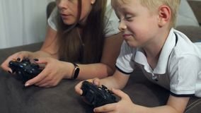 Mother and son play computer games with joysticks lying on the couch. Close-up of a mother with a child enthusiastically playing video games lying at home on stock video footage