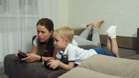 Mother and son play computer games with joysticks lying on the couch. Funny mom with a small child playing video games together, they lie on the couch at home stock footage