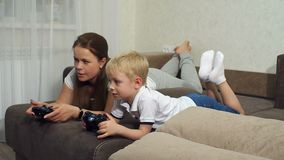 Mother and son play computer games with joysticks lying on the couch. A young mother with a small blond son playing computer games lying on the couch at home stock video