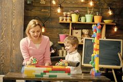 Mother and son play with constructor blocks. Mom and kid racing with plastic cars. Mommy talking to her boy while. Holding toy train. Nursery with chalkboard on stock photos