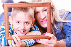 Mother and son play with empty frame. Royalty Free Stock Image