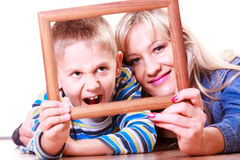 Mother and son play with empty frame. Spending time family bonds parenthood. Mother and son have fun play with empty picture frame hold in hand lay on floor Stock Photography