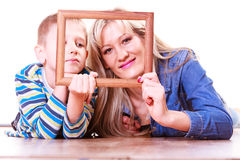 Mother and son play with empty frame. Spending time family bonds parenthood. Mother and son have fun play with empty picture frame hold in hand lay on floor Royalty Free Stock Photography
