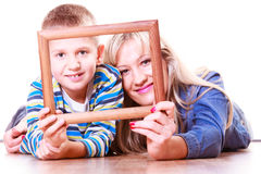 Mother and son play with empty frame. Spending time family bonds parenthood. Mother and son have fun play with empty picture frame hold in hand lay on floor Royalty Free Stock Image