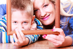 Mother and son play with empty frame. Spending time family bonds parenthood. Mother and son have fun play with empty picture frame hold in hand lay on floor Stock Images