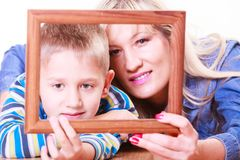 Mother and son play with empty frame. Spending time family bonds parenthood. Mother and son have fun play with empty picture frame hold in hand lay on floor Royalty Free Stock Photo