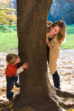 Mother and son play hide-and-seek. In autumn park Stock Photography