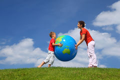 Mother with son play an inflatable globe. In  day-time stand  on  grass Royalty Free Stock Images