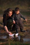 Mother and son play paper boats. In puddle Royalty Free Stock Images