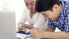 Mother and son play and watching smartphone ,Dolly shot of happy asian family with smily face at home . Mother and son are play and watching smartphone ,Dolly stock footage