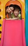 Mother and son at playground smiling. Mother and son at top of slide at playground, smiling, looking at camera Royalty Free Stock Photo
