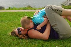 Mother and son playing. Outdoors on grass Stock Image