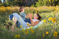 Mother and son playing. On a blanket in nature Royalty Free Stock Photos