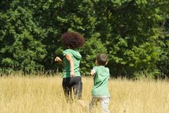 Mother and son playing. Mother playing with her son in a meadow, in a sunny day Royalty Free Stock Photo