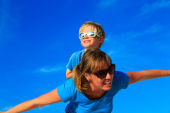 Mother and son playing airplane on blue summer sky Stock Images