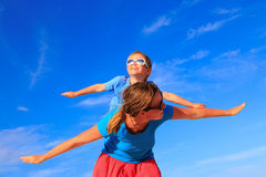 Mother and son playing airplane on blue summer sky Stock Photos