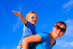Mother and son playing airplane on blue summer sky Stock Photography