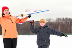Mother and son playing with an airplane at winter Stock Photo