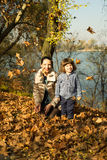 Mother and son playing with autumn leaves Royalty Free Stock Image