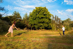 Mother and son playing badminton. During a sunny summer day in the park Royalty Free Stock Photography