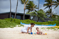 Mother and son playing on the beach. Young mother playing with her little son on a tropical beach Royalty Free Stock Photos