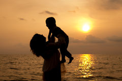 Mother and son playing on the beach in dawn time Royalty Free Stock Photos