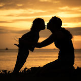Mother and son playing on the beach. At the sunset time Stock Photos