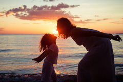 Mother and son playing on the beach at the sunset time. Concept of friendly family Royalty Free Stock Photos